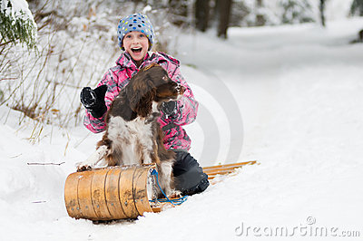 Girl and her dog on  a toboggan