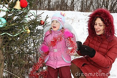 Girl with her mother is decorating christmass tree