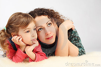 Girl and her mother lies on fell, hands on chin