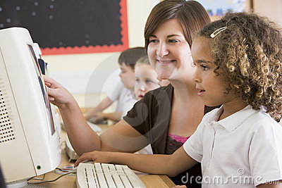 A girl and her teacher working on a computer