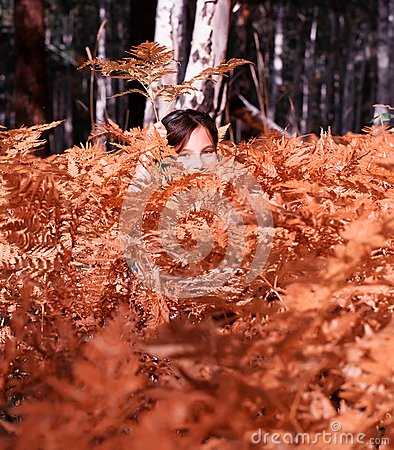 Girl hiding in autumn forest
