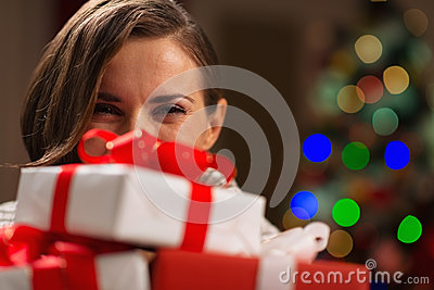 Girl hiding behind Christmas present boxes