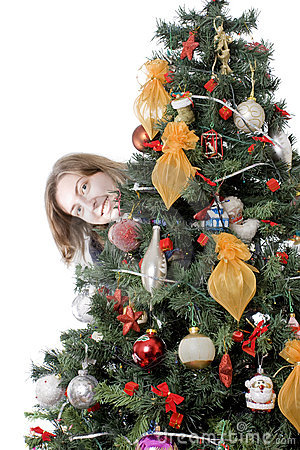 Girl hiding behind christmas tree