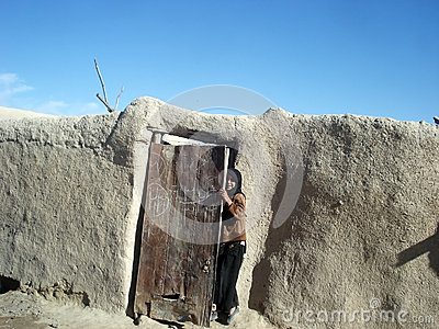 Girl hiding behind a door in Afghanistan Editorial Photo