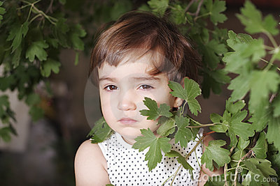 Girl hiding behind leaves