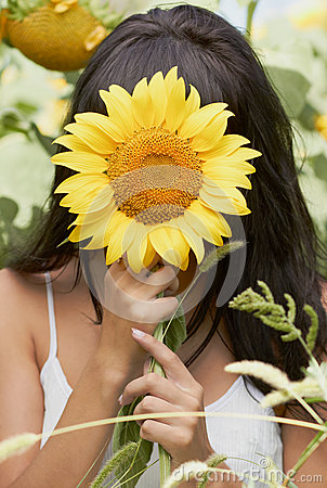 Girl hiding behind sunflower