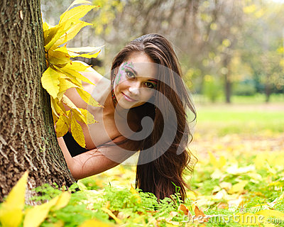 Girl hiding behind a tree
