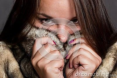 Girl hiding in fur coat