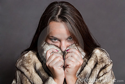 Girl hiding in fur coat