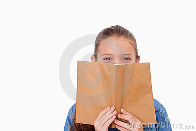 Girl hiding her face behind a book