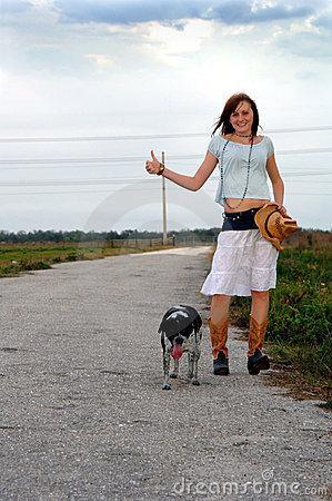 Girl hitchhiking with her dog