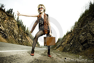 Girl hitchhiking with suitcase
