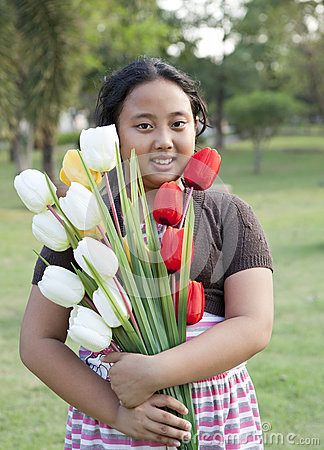 Girl hold bouquet of tulip flowers standing in ther garden