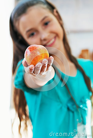 The girl is holding the apple