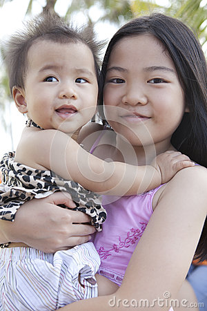 Girl holding baby on location