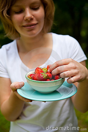 Girl holding a bowl of strawberries