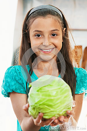The girl is holding the cabbage