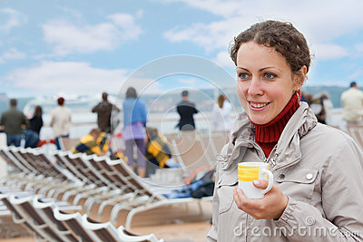 Girl holding cup on deck of big ship