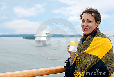 Girl holding cup on deck of ship