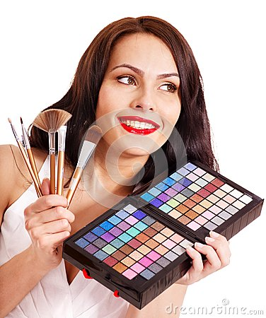 Girl holding eyeshadow and makeup brush.