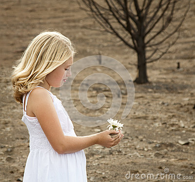 Girl holding flower in baren landscape