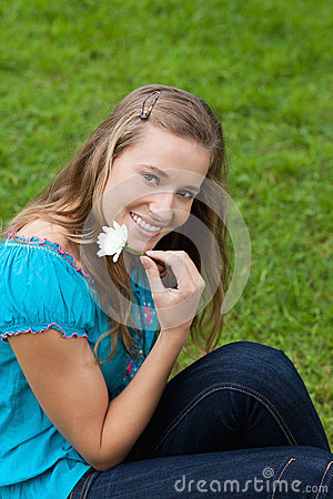 Girl holding a flower next to her face