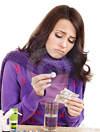 Girl holding glass of water and taking pills.