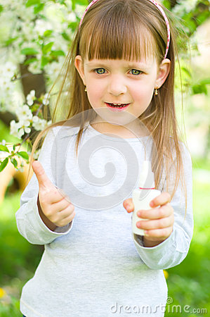 Girl holding nasal spray,showing thumbs up