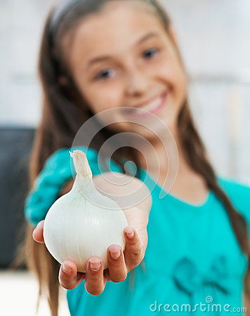 The girl is holding the onion