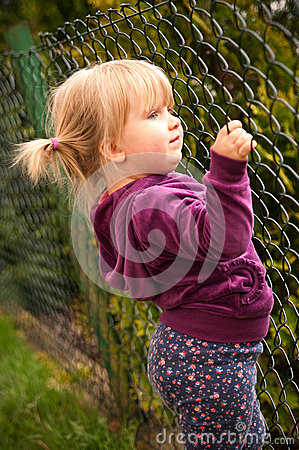 Girl holding onto fence