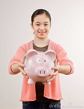 Girl holding piggy bank full of savings