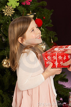 Girl Holding Present In Front Of Christmas Tree