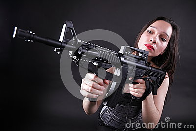 Girl holding Rifle on black background