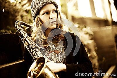 Girl holding saxophone, looking far away