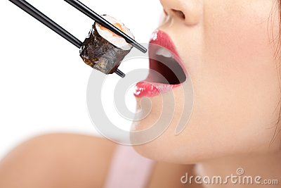 Girl holding sushi with a chopsticks, closeup