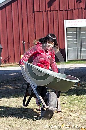 Girl holding wheelbarrow