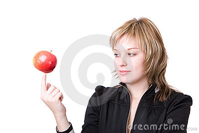 Girl holds an apple on a finger