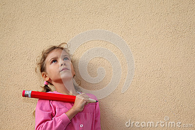 Girl holds big pencil and looks up near wall