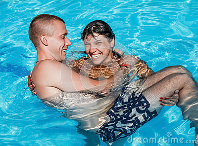 A girl holds a guy in her arms while standing in the pool