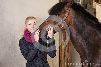 Girl holds the head of her pony