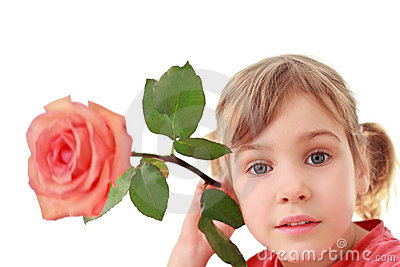 Girl holds  large rose near an ear, focus on face