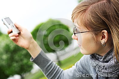 The girl holds a mobile phone in hands