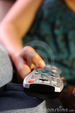 Girl holds remote control for TV
