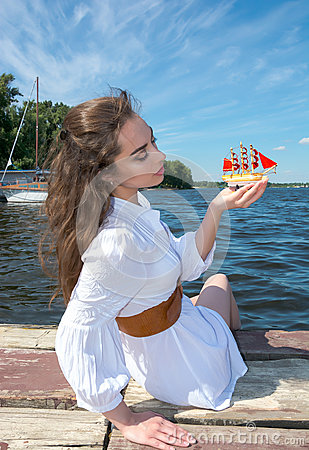 Girl holds a small ship with red sails.  Modern Assol.