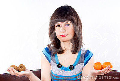 Girl holds a tangerine and kiwi