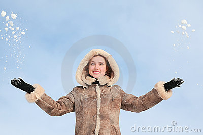 Girl in hood throws hands snow upwards