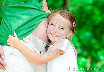 Girl hugging mother s belly