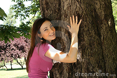 Girl hugging tree in garden