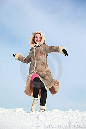 Girl hurries forward on snow and swings arms