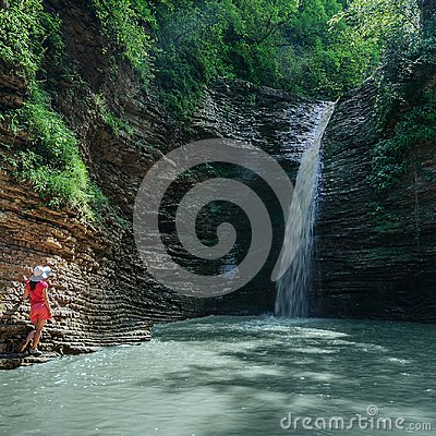 Free Girl In Red Looks At The Waterfall Maiden Spit On The Stream Rufabgo, Adygea, Russia Stock Images - 111975944
